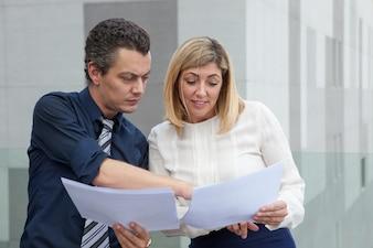 Zwei männliche und weibliche Kollegen, die draußen Dokumente besprechen