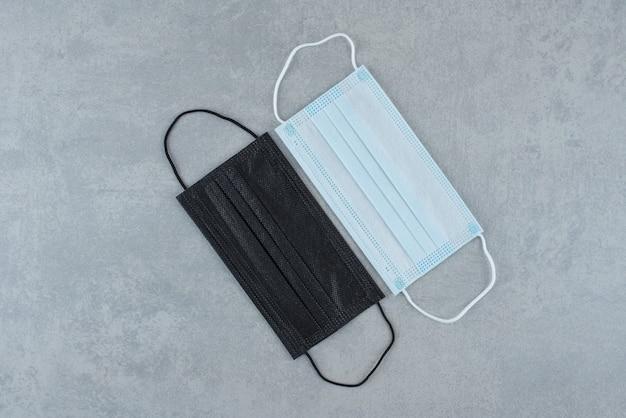 Zwei medizinische schutzmasken auf grauem hintergrund. foto in hoher qualität
