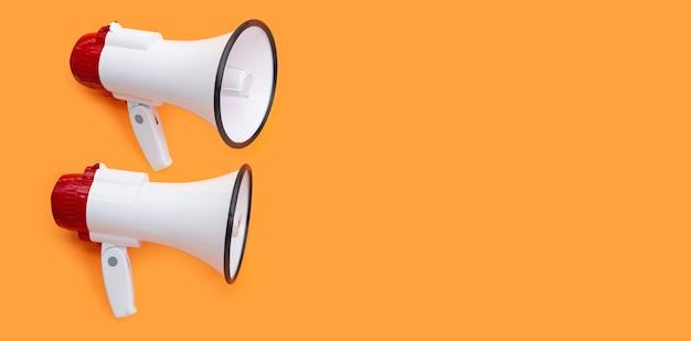 Zwei megaphone auf orangem hintergrund. platz kopieren