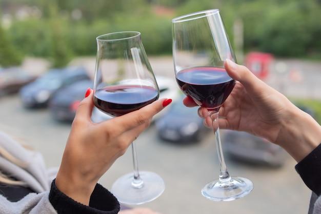 Zwei menschen klirren mit gläsern rotwein, feiern erfolg oder sprechen toast im weinrestaurant, gegen gestelle mit weinflaschen, nahaufnahme.