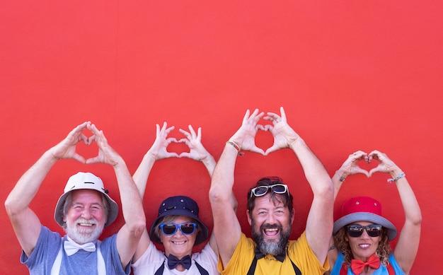 Zwei menschenpaare mit erhobenen armen bilden mit ihren händen ein herz. gemeinsam in freundschaft und liebe. bunte kleidung. rote wand im hintergrund