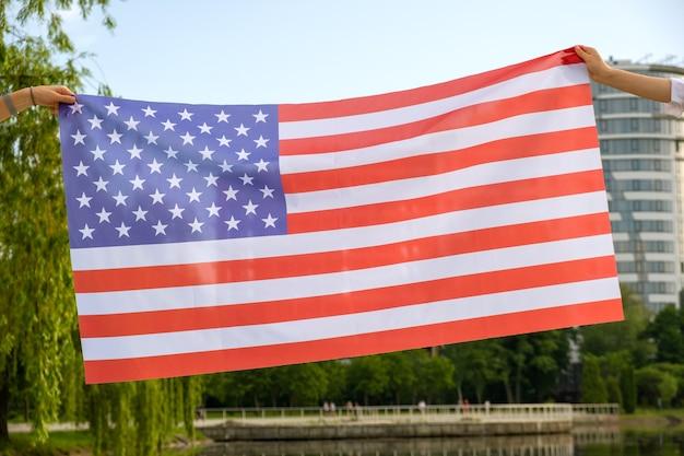 Zwei menschliche hände, die usa-nationalflagge halten. feier des internationalen tages des demokratiekonzepts.