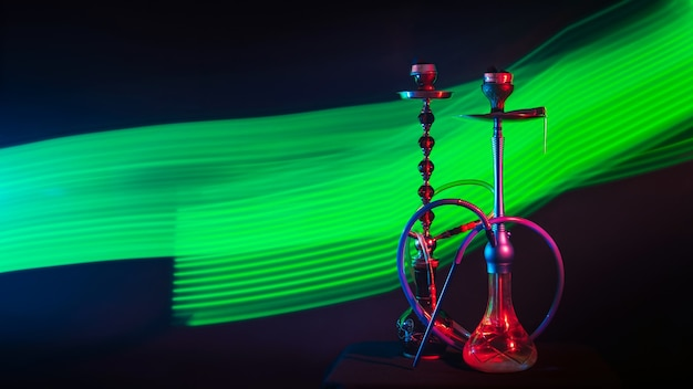 Zwei metall-wasserpfeifen mit glasflaschen mit shisha-holzkohlen im rauch mit grünem neonlicht auf dunklem hintergrund