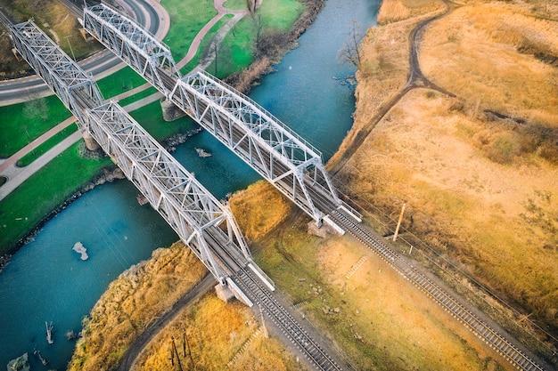 Zwei metallbrücken mit einem eisenbahnnetz über einem kleinen fluss, eine bank grün, mit rasen, die andere gelb, mit trockenem gras. kontrastierende landschaft. drohnenansicht.