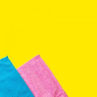 Zwei mikrofaserstaubgewebe liegen auf einem hellen gelben hintergrund. set von haushaltsgeräten.