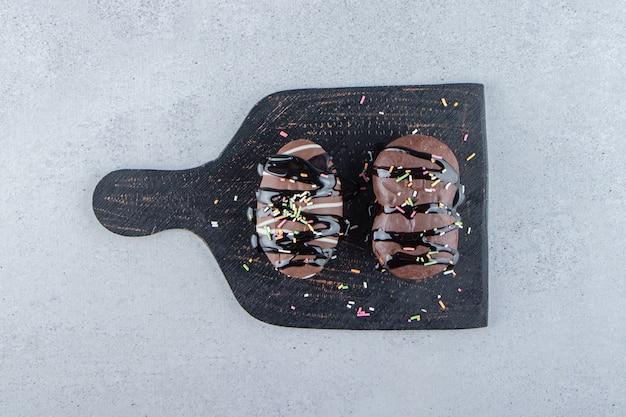 Zwei mini-schokoladenkuchen mit streuseln auf schwarzem schneidebrett. foto in hoher qualität