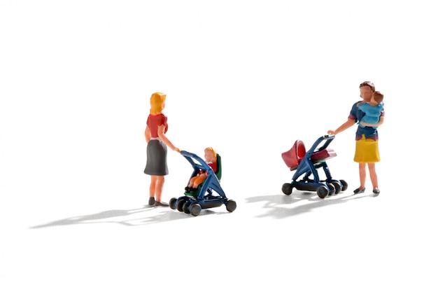 Zwei miniaturfiguren junger mütter und babys