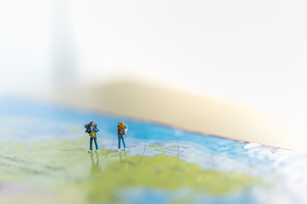Zwei miniaturfiguren mit rucksack auf weltkarte