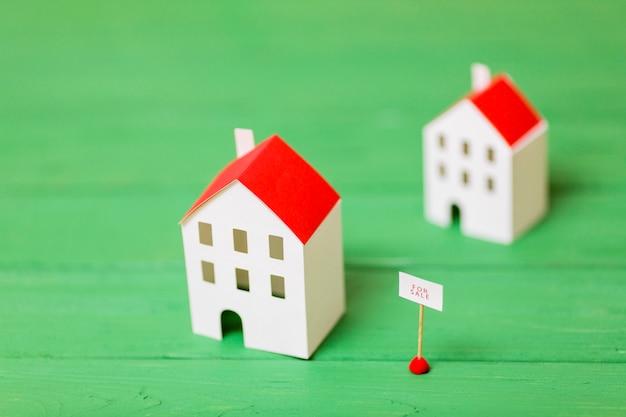Zwei miniaturhausmodelle für verkauf auf hölzernem grünem schreibtisch