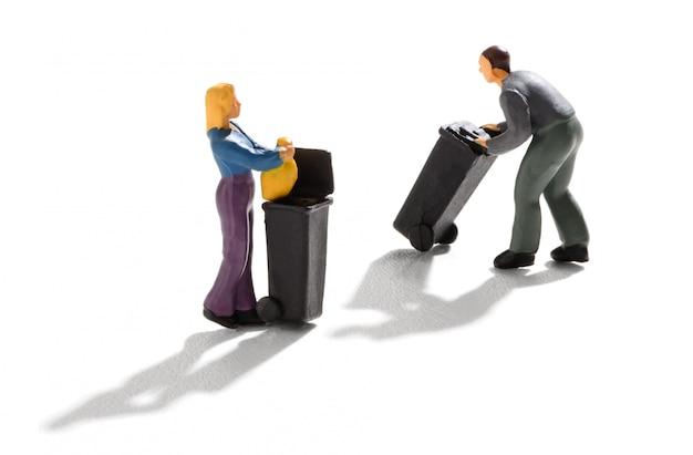 Zwei miniaturmenschen, die mülleimer benutzen