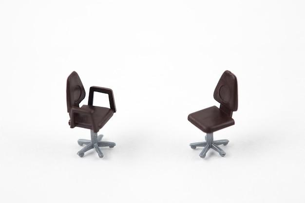 Zwei miniaturstühle auf weißem hintergrund