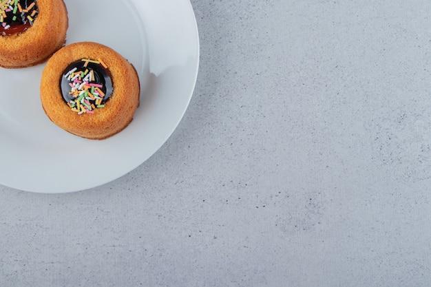 Zwei minikuchen mit gelee auf weißem teller. foto in hoher qualität