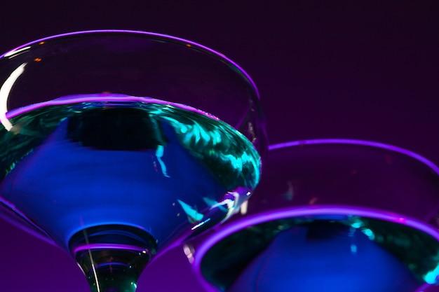 Zwei mit wein gefüllte gläser stehen auf dem tisch im studio. lebendige helle farbige beleuchtung. trendige 2018 ultra violet glühbirne. kunstdekoration mit mystischem farbton