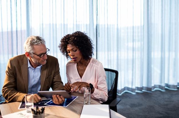 Zwei mitarbeiter, die an einem tablet-computer arbeiten