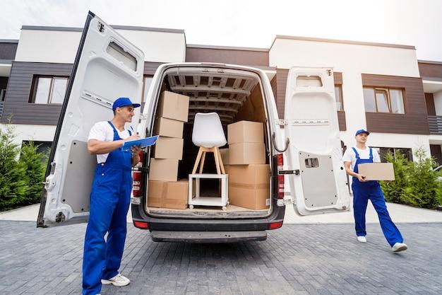 Zwei mitarbeiter einer umzugsfirma laden kisten und möbel in einen kleinbus