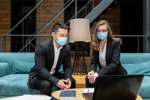 Zwei mitarbeiter eines internationalen unternehmens diskutieren einen bericht über die arbeit