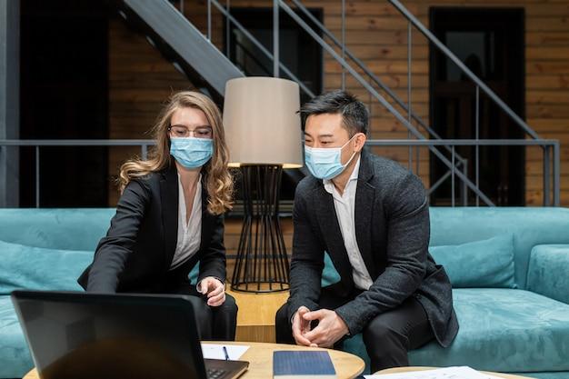 Zwei mitarbeiter eines internationalen unternehmens diskutieren einen bericht über die geleistete arbeit eines asiatischen mannes und einer asiatischen frau