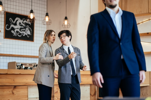 Zwei mitarbeiter starren und klatschen über ihren männlichen kollegen im büro