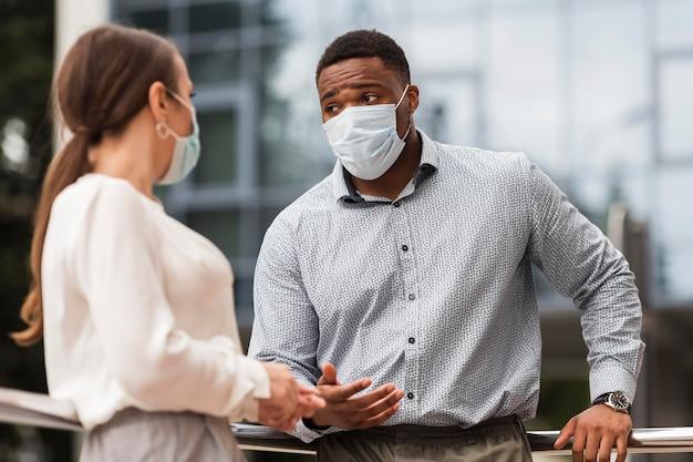 Zwei mitarbeiter unterhalten sich im freien während einer pandemie mit masken