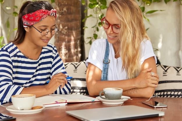 Zwei mitarbeiterinnen unterhalten sich, machen sich notizen im notizblock, trinken aromatischen kaffee
