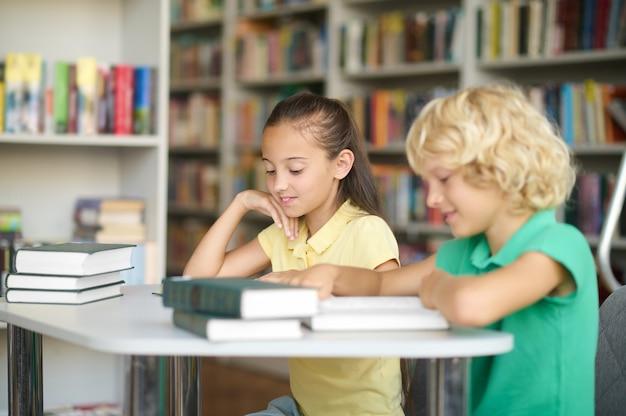Zwei mitschüler studieren in einer öffentlichen bibliothek