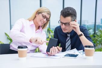 Zwei mittlere erwachsene Geschäftskollegen, die Telefon Café am im Freien verwenden.