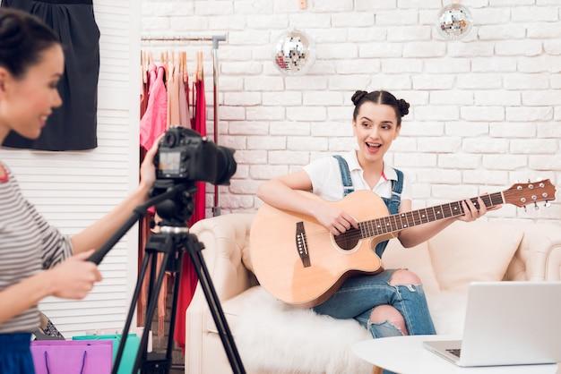 Zwei mode-blogger-mädchen spielen gitarre vor der kamera.