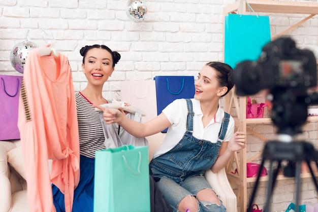 Zwei mode-blogger-mädchen zeigen auf buntes kleid.