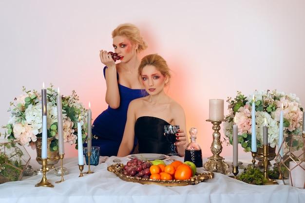 Zwei mode-modelle hinter dem tisch mit früchten, kerzen und wein.