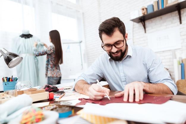 Zwei modedesigner, die ausschnitt auf leder machen.