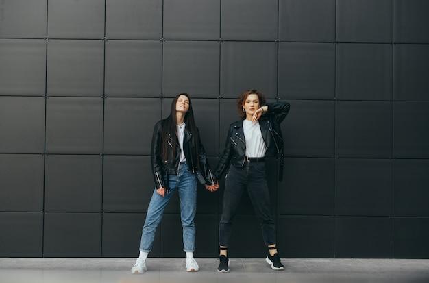 Zwei modelle in straßenkleidung posieren gegen eine dunkle wand