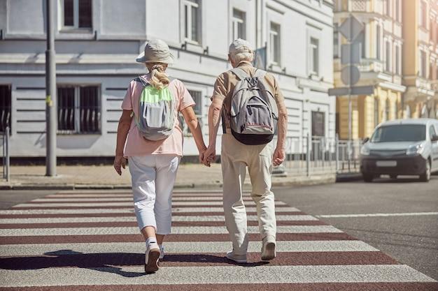 Zwei moderne ältere kaukasische touristen, die die straße im stadtzentrum überqueren