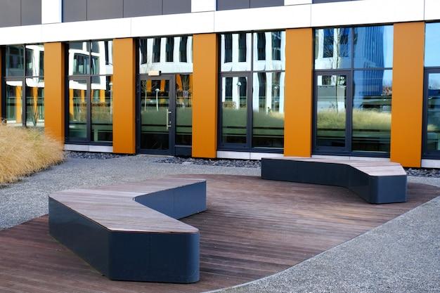 Zwei moderne bänke in einem innenhof des zeitgenössischen gebäudes des geschäftsviertels.