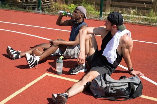 Zwei moderne basketballspieler, die sich vor gericht entspannen