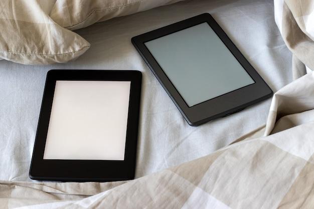 Zwei moderne elektronische bücher mit leeren bildschirmen auf einem weiß-beigen bett. mockup tabletten auf bettwäsche