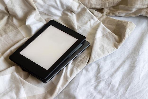 Zwei moderne elektronische bücher mit leeren leeren bildschirmen auf einem weiß-beigen bett. mockup-tabletten übereinander auf der bettwäsche
