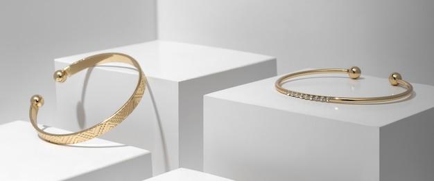 Zwei moderne goldene armbänder auf weißen geometrischen würfeln
