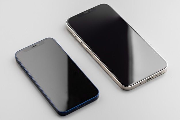 Zwei moderne smartphones mit schwarzem bildschirm auf grau