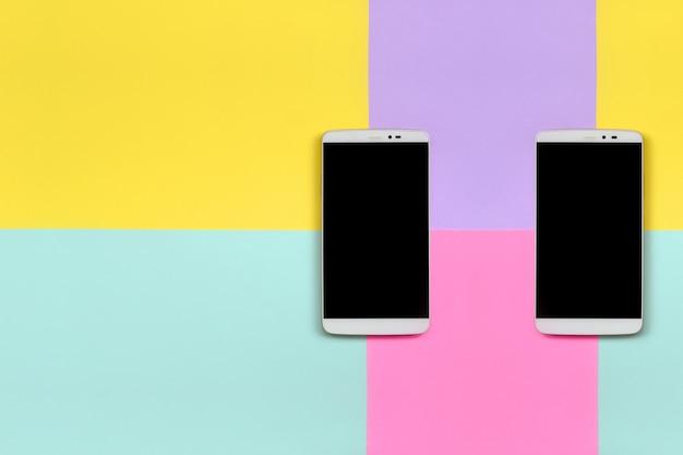 Zwei moderne smartphones mit schwarzen bildschirmen auf beschaffenheitshintergrund