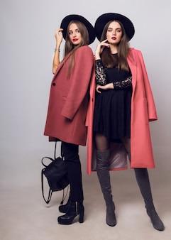 Zwei modische junge frauen in lässigem, trendigem frühlingsmantel, stiefeln mit absätzen, schwarzem hut und stilvoller handtasche