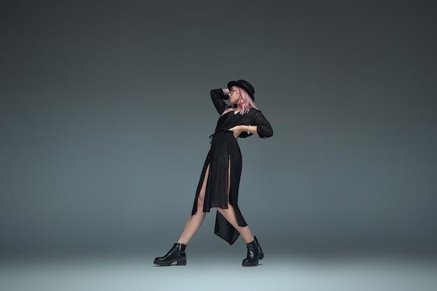 Zwei modische mädchen, die schwarze trendige outfits tragen, posieren