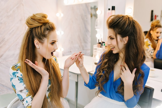 Zwei modische models mit stilvollem make-up, luxuriöse frisuren, die gemeinsam spaß im friseursalon haben