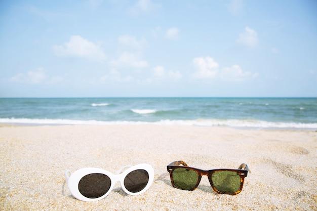 Zwei modische sonnenbrillen schließen auf dem strandsand im sommer.