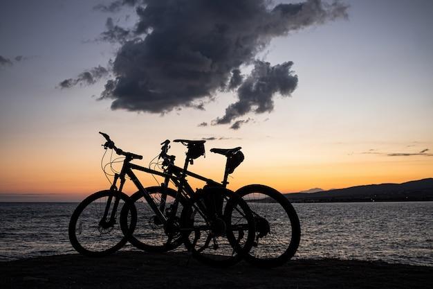 Zwei mountainbikes stehen am rand einer klippe, wo sie einen leuchtend orangefarbenen sonnenuntergang, berge und große wolken sehen können. erholung und sport in der kurstadt gelendzhik