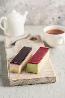 Zwei moussekuchen mit unterschiedlichem zuckerguss auf einem holzbrett mit einer teekanne und einer tasse tee