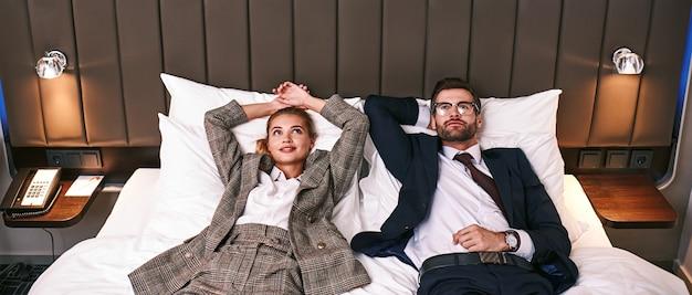 Zwei müde geschäftsleute, die in einem hotelzimmer auf dem bett liegen