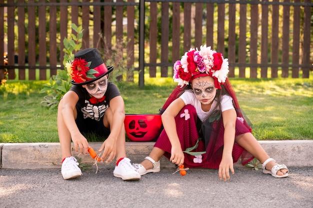 Zwei mürrische kleine freunde in halloween-kostümen, die sie ansehen, während sie auf der straße vor der kamera gegen das holztor sitzen und süßigkeiten haben