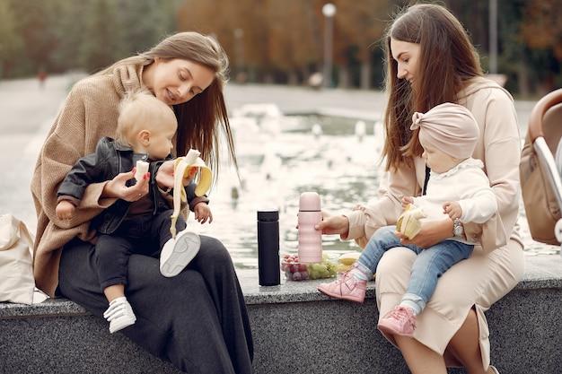Zwei mütter mit kleinen kindern verbringen zeit in einem park
