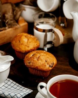Zwei muffins mit rosinen, serviert mit schwarzem tee