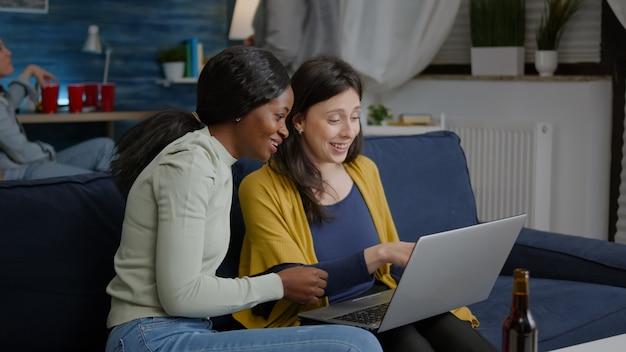 Zwei multiethnische frauen sitzen auf der couch und schauen sich comedy-serien auf dem laptop an